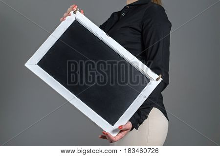 Woman holding tilted chalkboard on a dark gray background. Free blank empty copy space for text, menu or specials. Waitress in a restaurant or business person. Black texture for content.