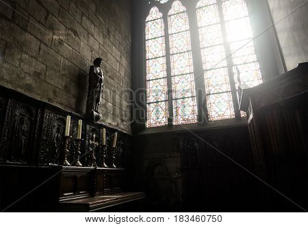 PARIS - MARCH 12, 2017: Interior of Notre Dame with a Jesus statue and a ray of light from the window. The cathedral of Notre Dame is one of the main attractions for tourists in France.