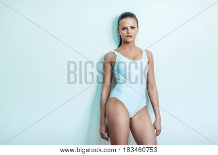 Beautiful sexy girl with tattoo in white bodysuit standing on a white background. Mock up.
