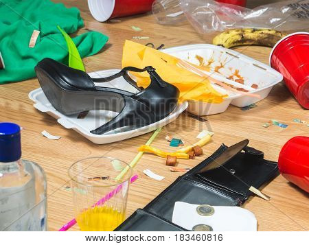 High heels, food leftovers and trash everywhere after awesome party. Next morning regret and remorse. Messy home needs cleaning. Funny hangover and wild partying concept.