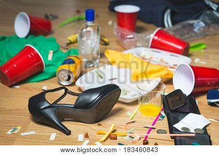 Terrible mess after party. Trash, bottles, food, cups and clothes on the floor. Messy apartment after guests leaving or the next morning. Horrible chaos after crazy wild night. Hangover concept.