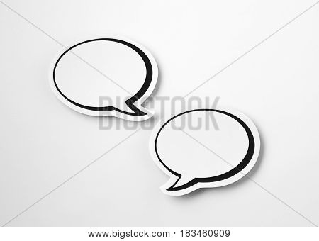 2 blank speech bubbles on white paper background. Chat bubble cut from cardboard. Simple and effective design. Discussion, chat and commenting concept with a lot of free empty copy space for text.