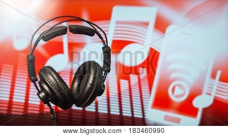 Large black headphones in front of a modern blurred background with notes, equalizer and a smartphone icon. An abstract online music streaming and listening concept with free copy space for text.