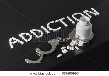 Get addicted to drugs or free from addiction to medicine. Drug and narcotics abuse or after rehab concept. Addiction written with pills. Medicine spilling out from a bottle locked with open handcuffs.