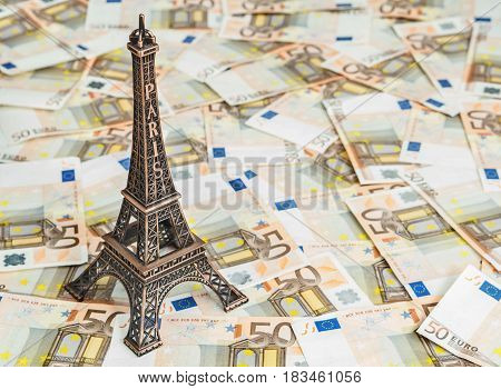 Travel budget concept with copy space. Eiffel Tower souvenir and vacation money. Savings for trip to France.