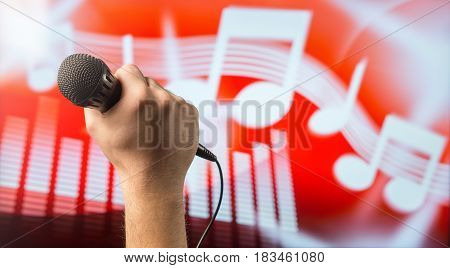 Man holding microphone in front of an abstract music and note background. Karaoke or singing contest theme. Vocal coaching or live singing concept with copy space for text.