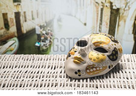 Mask from Venice with a gondolier rowing a gondola in a narrow canal in the blurred background. Golden and ornamental souvenir with traditional and beautiful Venetian view. Summer holiday concept. button, icon or banner for website, social media or brochu