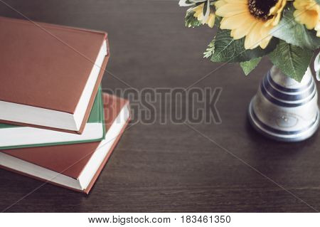 Three books with flowers on a wood table.