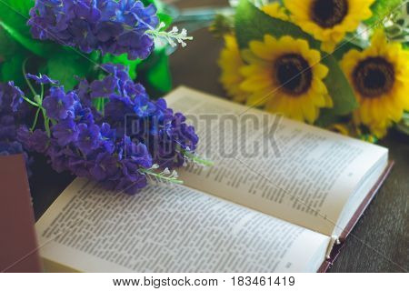 Opened book with yellow and purple flowers on a wood table.