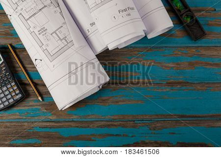 Paper scrolls, pencil, calculator and spirit level on wooden plank