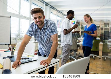 Graphic designer smiling at camera while colleague interacting in background at office