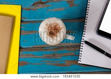 Coffee mug, notepad, smartphone, pen and diary on wooden plank