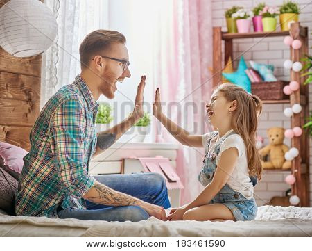 Happy father's day! Dad and his daughter child girl are playing and laughing. Family holiday and togetherness.