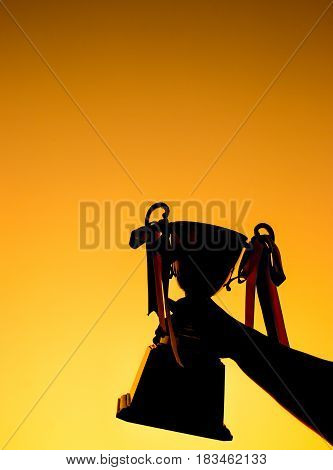 winner and champion concept Silhouette of Hand holding championship trophy against yellow sky