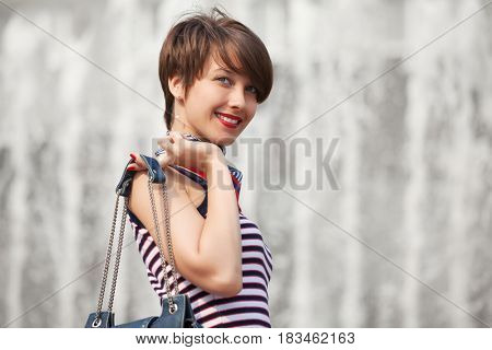 Happy young woman with handbag walking in city street. Stylish fashion model in tank top with pixie hairstyle outdoor