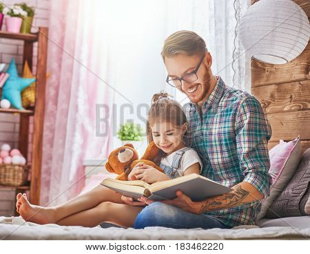 Father and child on the bed in kids room. Handsome young daddy reading a book to his daughter. Family holiday and togetherness.