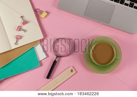 Cup of tea, laptop, magnifying glass, diaries, ruler and paper clips on pink background