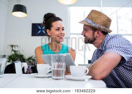 Happy couple using digital tablet in café