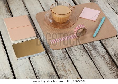 Cup of tea, sticky notes, diary, notepad, printed sellotape and pen on wooden plank