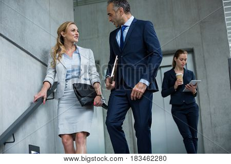 Business colleagues talking to each other while walking down stairs in office building