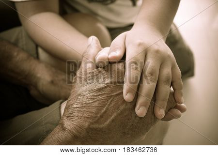 Hands of a little kids holding elderly man World Kindness Day concept and Adult day care center week
