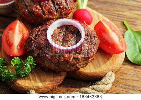 Homemade beef burger with onion, vegetables on cutting board