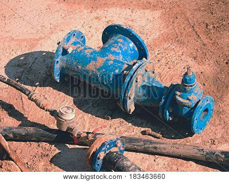 Old drink water pipes used blue gate valve and reduction joint members. Water supply interrupted repairing of infrastructure. Metal corrosion texture. PVC pipeline.
