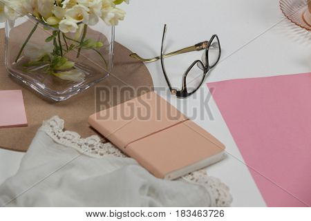 Spectacles, diary, cloth, blank page, paper balls and flowers on white background