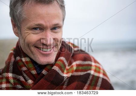 Portrait of smiling man wrapped in shawl at beach