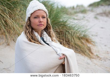 Thoughtful woman wrapped in shawl at the beach