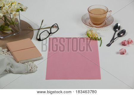 Cup of tea, spoons, spectacles, diary, cloth, blank page, paper balls and flowers on white background