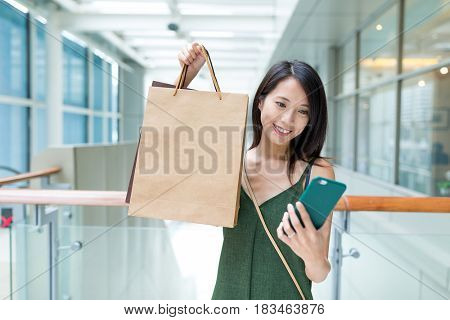 Woman holding shopping bag and using cellphone