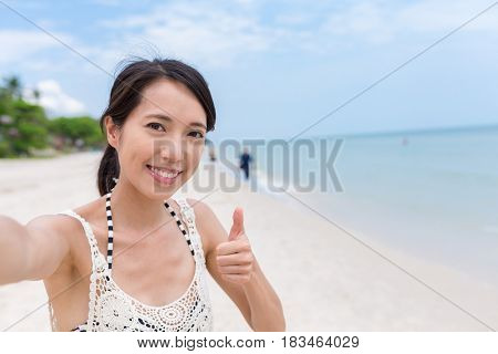 Woman taking selfie at the beach