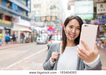 Woman taking selfie by cellphone in Mongkok city of Hong Kong
