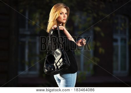 Young blond business woman with handbag walking in night city street. Stylish fashion model in black jacket and blue jeans outdoor