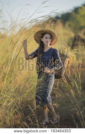 Asian farmer woman walking back home after work