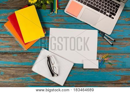 Notepad, blank page, spectacles, diaries, pens, color pencils, laptop and paper pins on wooden plank
