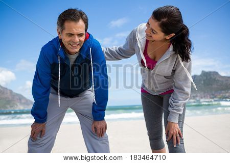 Happy couple taking a break after jogging on beach