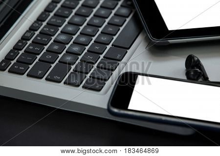 Close-up of laptop, digital tablet, smartphone and earphones