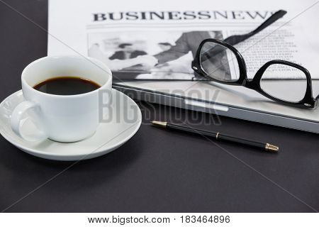 Cup of coffee, spectacles, closed laptop, newspaper and pen on grey background