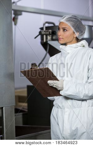 Female butcher maintaining records on clipboard at meat factory