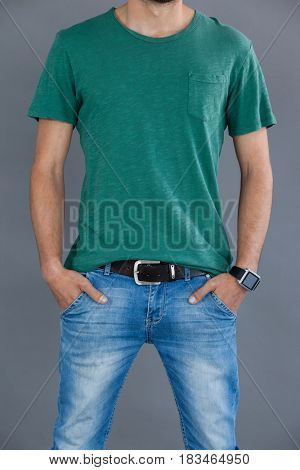 Mid-section of a man in green t-shirt posing with hands in pockets against grey background