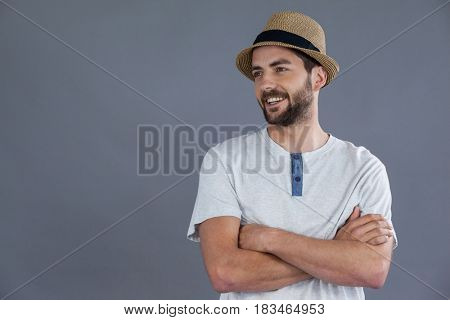 Happy man in white t-shirt and fedora hat posing against grey background