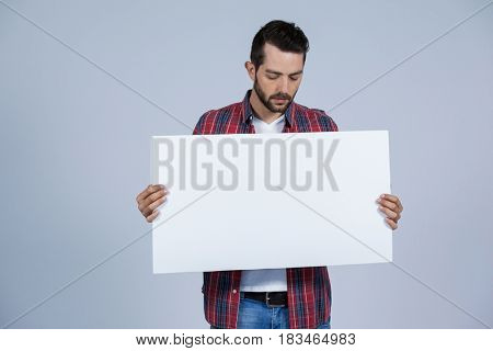 Man holding a blank placard against grey background