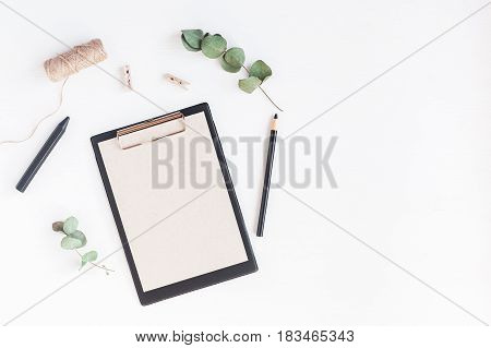 Workspace with paper blank pencils eucalyptus branches. Business concept. Flat lay top view