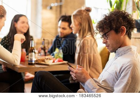 technology, lifestyle, holidays and people concept - man with smartphone and friends at restaurant