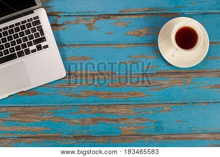 Cup of tea and laptop on old wooden plank