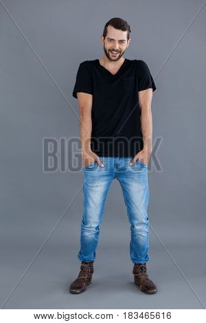Portrait of a man in black t-shirt and blue jeans standing against grey background