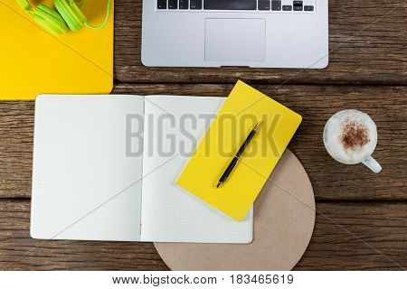 Laptop, diary, pen, coffee mug and headphones on wooden plank
