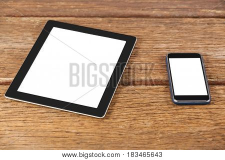 Close-up of digital tablet and smartphone on wooden plank